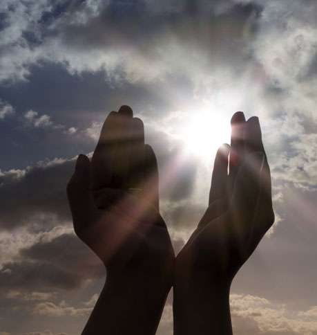 Hands are raised to heaven as the sun peeks through the clouds