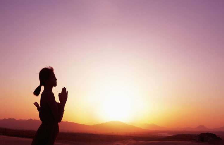 A woman stands in prayer as the sun sets in the background