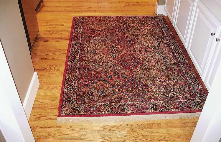 The rug has moved all the way from the hallway's left wall to the right wall, a distance of several inches.