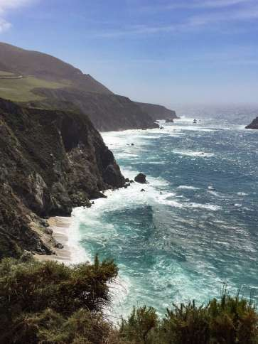 The surf pounds against the rising cliffs in Big Sur.