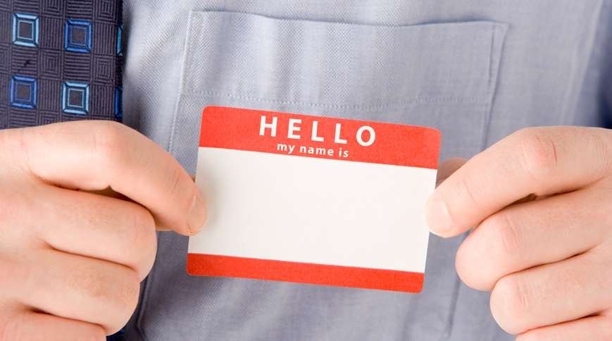 A man places a Hello My Name Is tag on his shirt pocket.