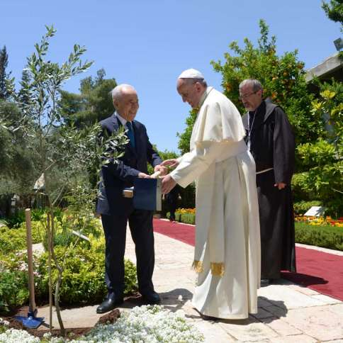 Pope Francis plants an olive tree in the garden of the official residence of the president of Israel. Former President Shimon Peres is on the right.