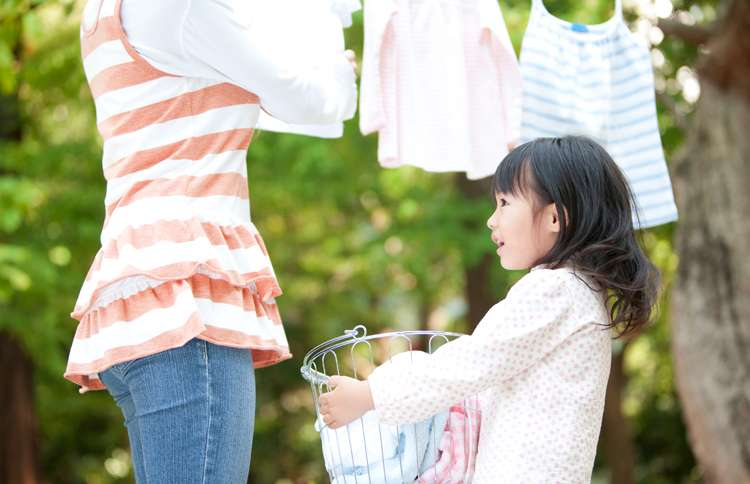 Guideposts: A young girl holds the laundry basket as her mother hangs the wash from the line