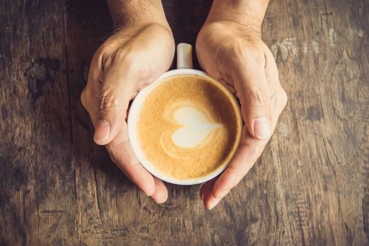 Guideposts: Two hands enfold a coffee cup with a heart shape in the foam