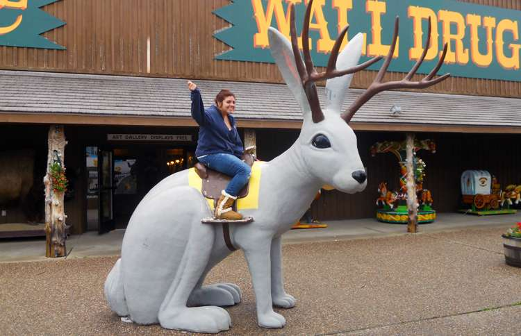 Guideposts: A tourist waves from her perch atop a giant jackalope at Wall Drug in Wall, South Dakota