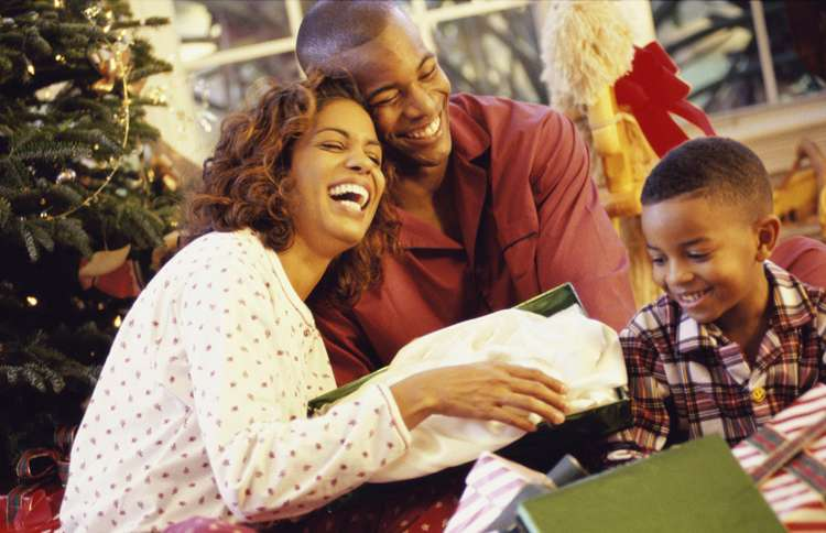 Guideposts: The members of a loving family smile as they open their Christmas presents