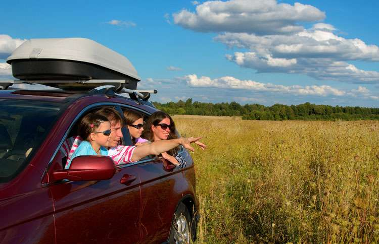 A family on a road trip gazes out to the horizon