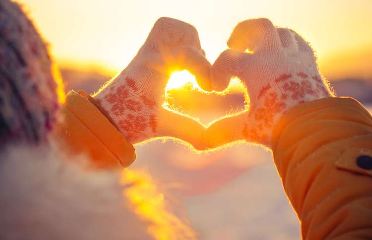Guideposts: Two mittened hands make a heart shape, with the sun on the horizon shining through