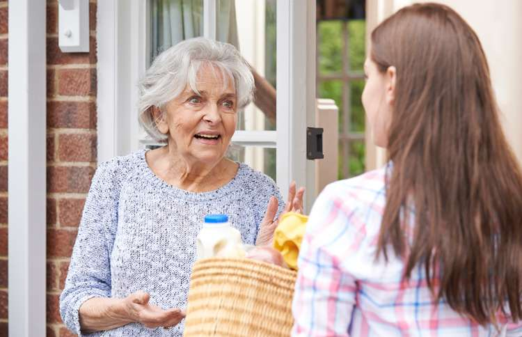 Guideposts: A young woman surprises a senior woman with a bag of groceries
