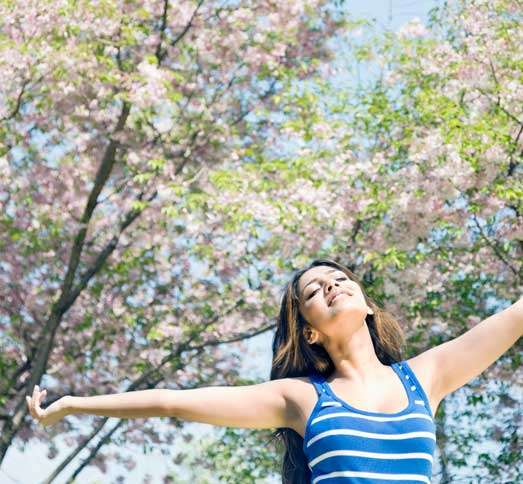Guideposts: A young woman with her arms outstretched revels in the delights of spring.