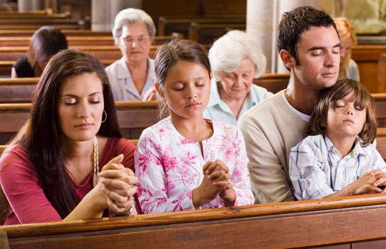A family bows its heads in prayer in church