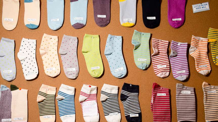 A board of socks hangs in Gina's office. Gina has transformed her parents' sock business, at the Emi-G Knitting mill in Fort Payne, Alabama.