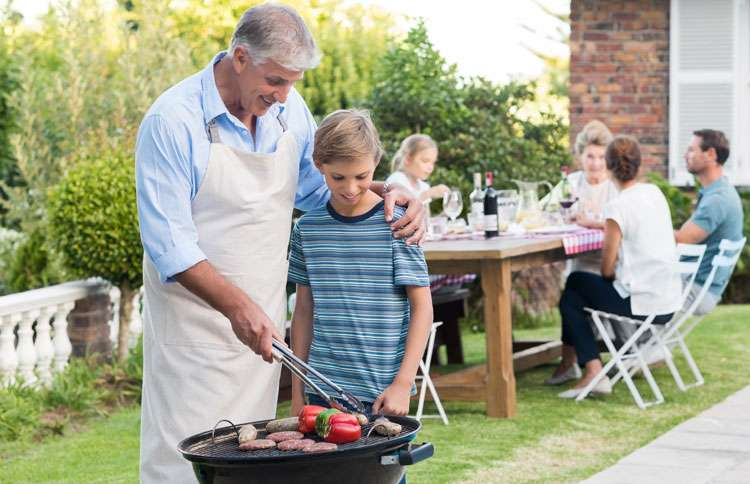 A grandfather teaches his grandson about grilling outdoors while the family looks on