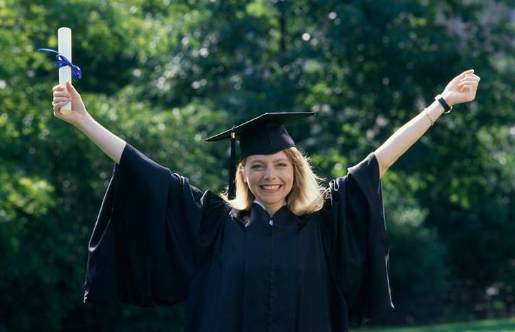 Guideposts: A woman graduating from college raises her arms in celebration