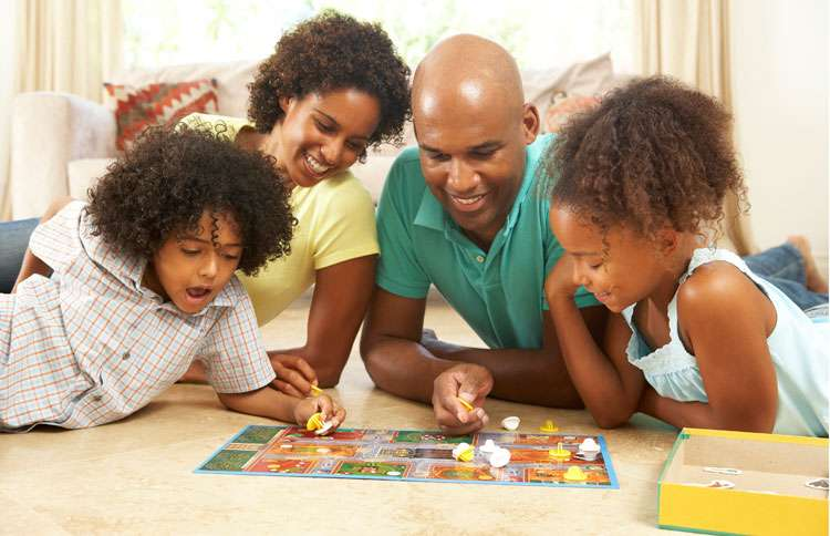 A smiling family is gathered around a board game