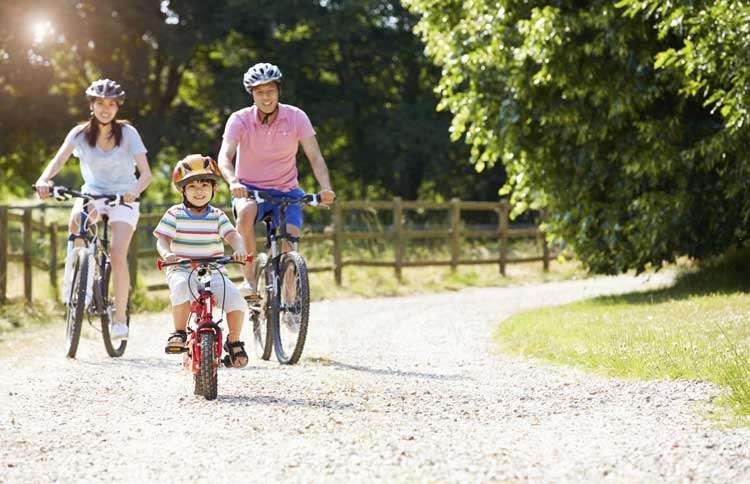 Guideposts: A young mother, father and child ride their bikes along a country lane