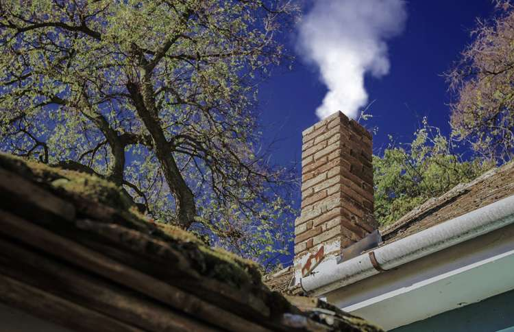 Guideposts: Wood smoke wafts skyward from the chimney of a suburban home.
