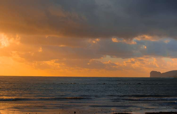 Guideposts: The warm glow of a sunrise shines down open the seashore.