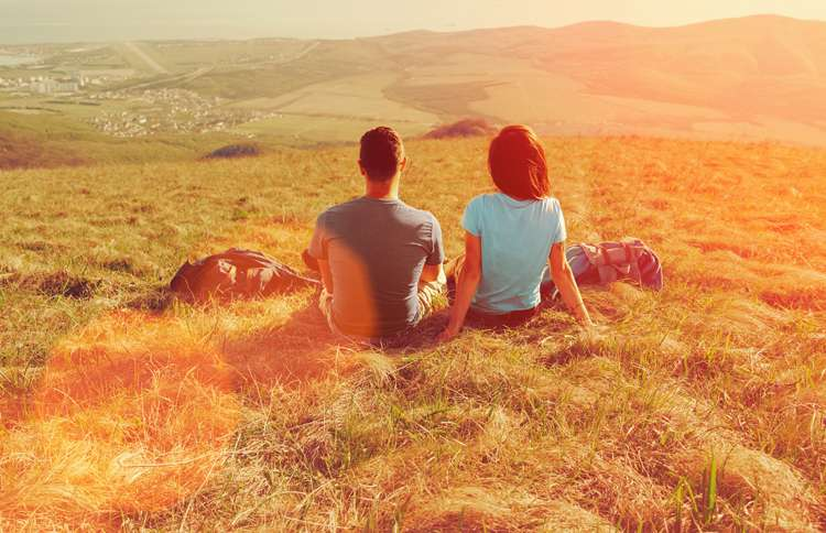 Guideposts: A man and a woman sit together in a sun-drenched field