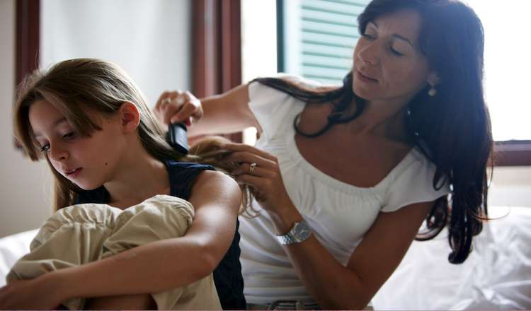 mom brushes daughter's hair. Author Amy Julia Becker learned 5 life lessons from her children.