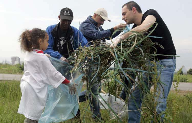 Guideposts: A young girl holds a trash bag open while a group of volunteers places tree trimmings in it.
