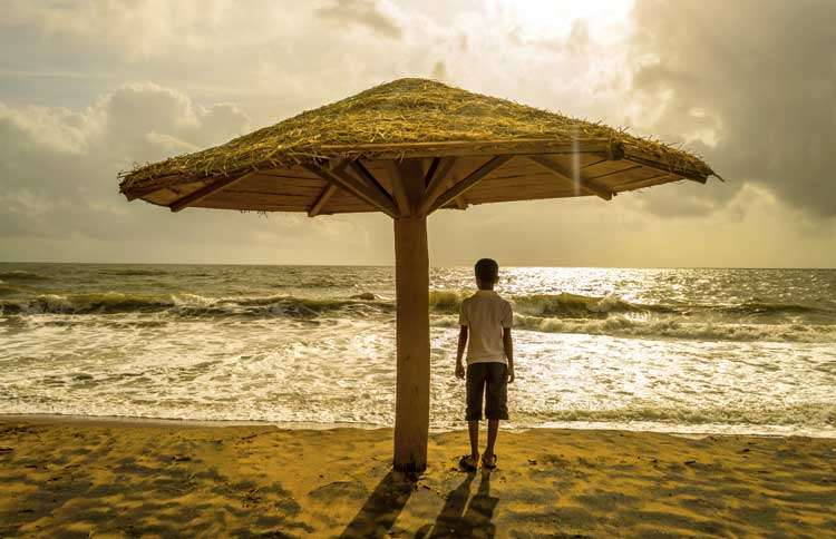 Guideposts: A young boy watches the sunset over the ocean from under a thatch beach umbrella