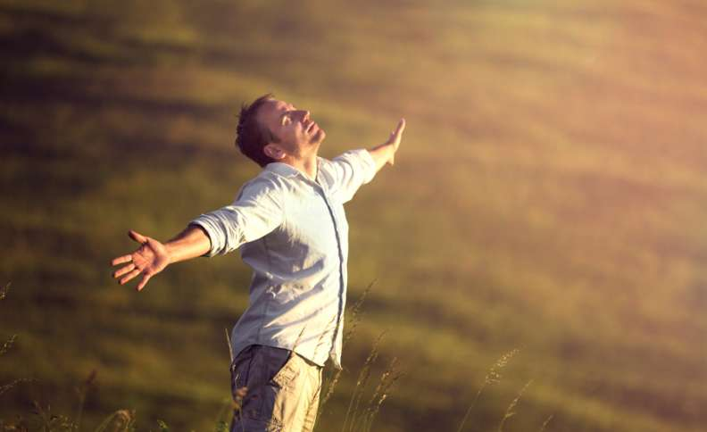 a man stretches his arms wide to feel the breeze