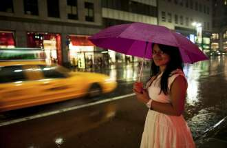 a woman in new york city with an umbrella prepared for a rainstorm