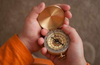 A child's hands clasp a brand new compass