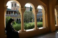 A nun sits quietly within the Abbaye Notre-Dame de l'Annonciation
