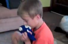 A young boy hugs his stuffed monkey