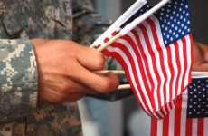 A veteran in combat fatiques holds a bundle of small American flags.