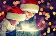 A mother and child in santa hats opening a present