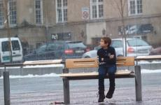 Boy sitting at a bus stop