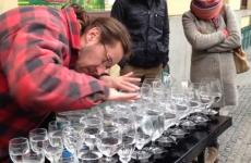 A street musician plays a tune on water-filled goblets.
