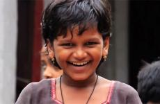 A young girl smiles joyfully.
