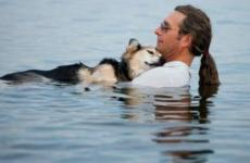 Man embracing his aging dog in Lake Superior. Photo by: Hannah Stonehouse Hudson