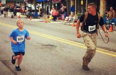 Myles Kerr encourages 9-year-old Brandon Fuchs in a 5K race.