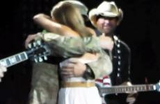 Toby Keith looks on as a military couple is reunited onstage during a concert
